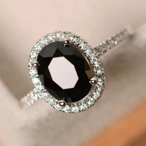 SILVER OVAL SHAPED ONYX / WHITE TOPAZ HALO RING